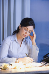 Hispanic businesswoman writing at desk