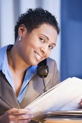 African businesswoman reading newspaper