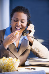 African businesswoman eating popcorn