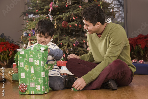 Hispanic father watching son open Christmas gift
