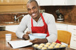 African American man baking with cookbook