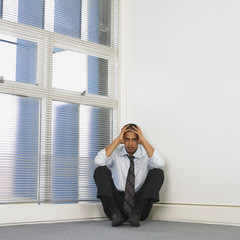 Mixed Race businessman sitting in corner