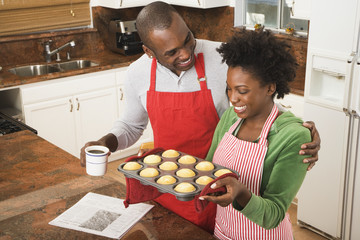 African American couple holding tray of muffins