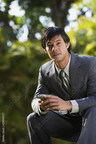 South American businessman sitting in park