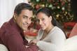 Hispanic couple sitting on sofa