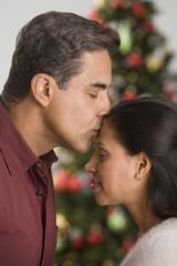 Hispanic man kissing wife on forehead