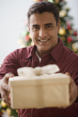 Hispanic man holding out gift