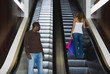 African man looking at woman on escalator