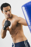Mixed Race man using punching bag