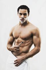 Mixed Race man in towel shaving