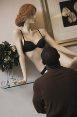 African man looking at lingerie mannequin