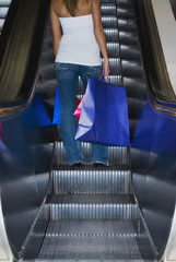 Woman on escalator with shopping bags