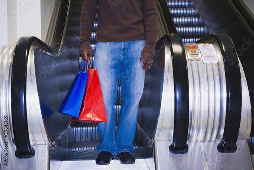 African man on escalator with shopping bags