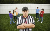 Hispanic referee between groups of girls and boys