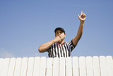 Hispanic referee blowing whistle over fence