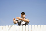 Hispanic referee making call over fence