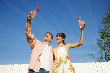 Multi-ethnic couple holding cocktails
