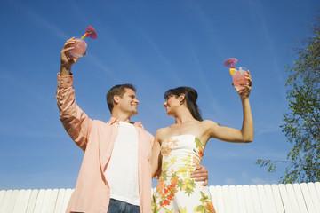 Multi-ethnic couple holding cocktails