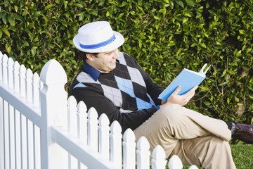 Man reading next to fence
