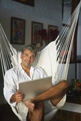 South American man holding laptop