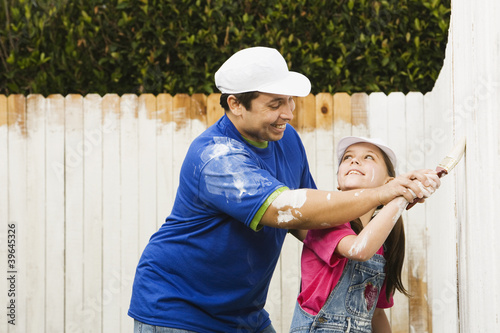 Hispanic father and daughter painting fence