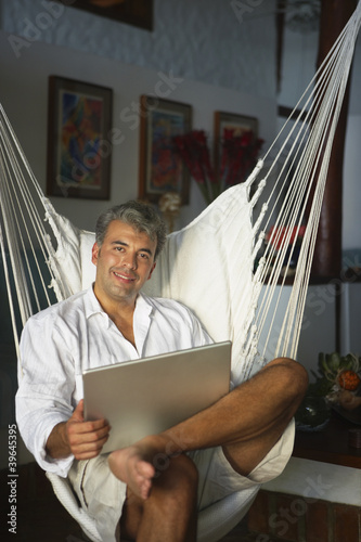 South American man holding laptop