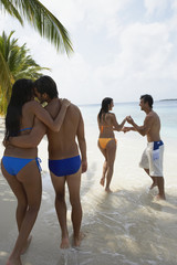 South American couples walking on beach