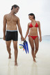 South American couple carrying snorkeling gear