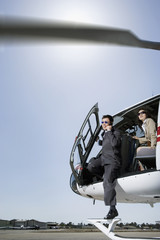 Asian businesspeople getting out of helicopter