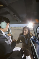 Asian businesswoman getting into helicopter
