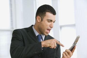 Hispanic businessman yelling at cell phone