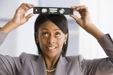 African American businesswoman holding level on head