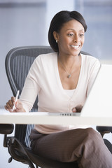 African American businesswoman looking at laptop