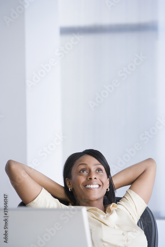 African American businesswoman with hands behind head