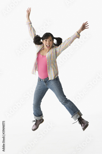 Chinese woman jumping with arms raised