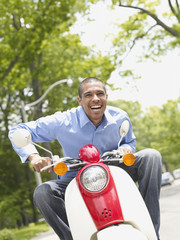 African American man riding motor scooter