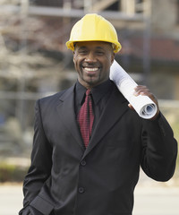 African American businessman holding blueprints