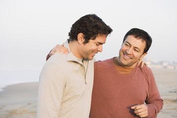 Hispanic friends walking on beach