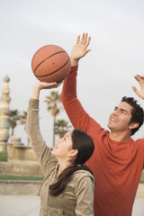 Hispanic father and daughter playing basketball