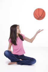 Ten year old Asian girl tossing basketball