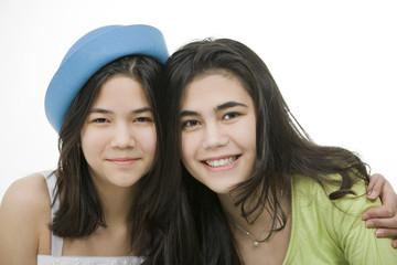 Two teen girls smiling together, hugging.