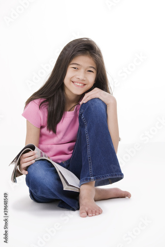 Little girl sitting on floor reading a magazine