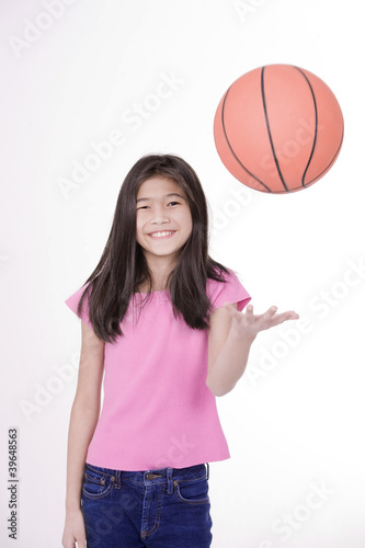 Ten year old Asian girl throwing basketball