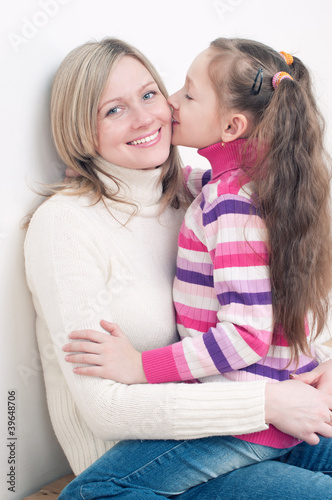 Happy young woman sitting on the floor with her little daughter