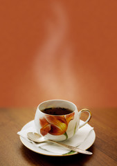 cup of hot tea on a brown background
