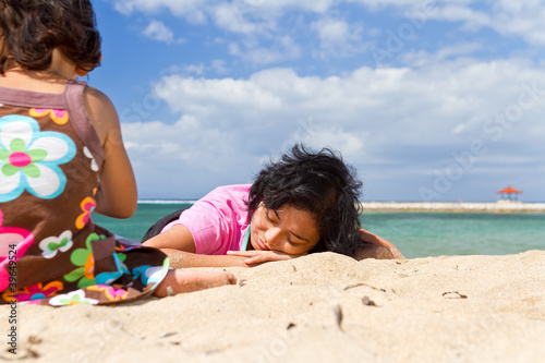 asian mother relaxing while child playing at the beach