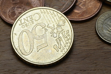 Some euro coins, on of fifty cent, on wooden table