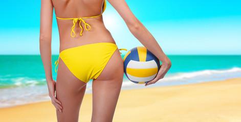 Woman with a ball on a beach