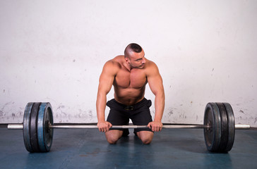 Man preparing to lift a heavy dumbbell