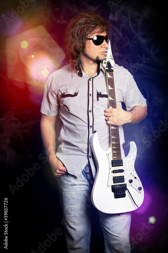 cute young rock musician with a white guitar